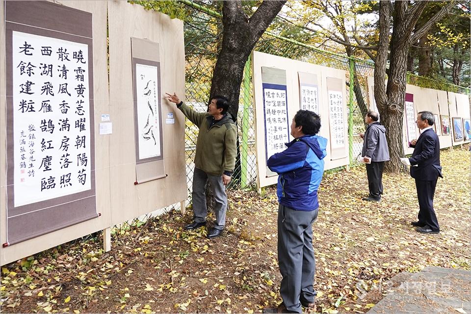 ▲ 전시된 작품을 설명하고 있는 장기학 작은숲도서관 TF팀장과 관람 주민들.