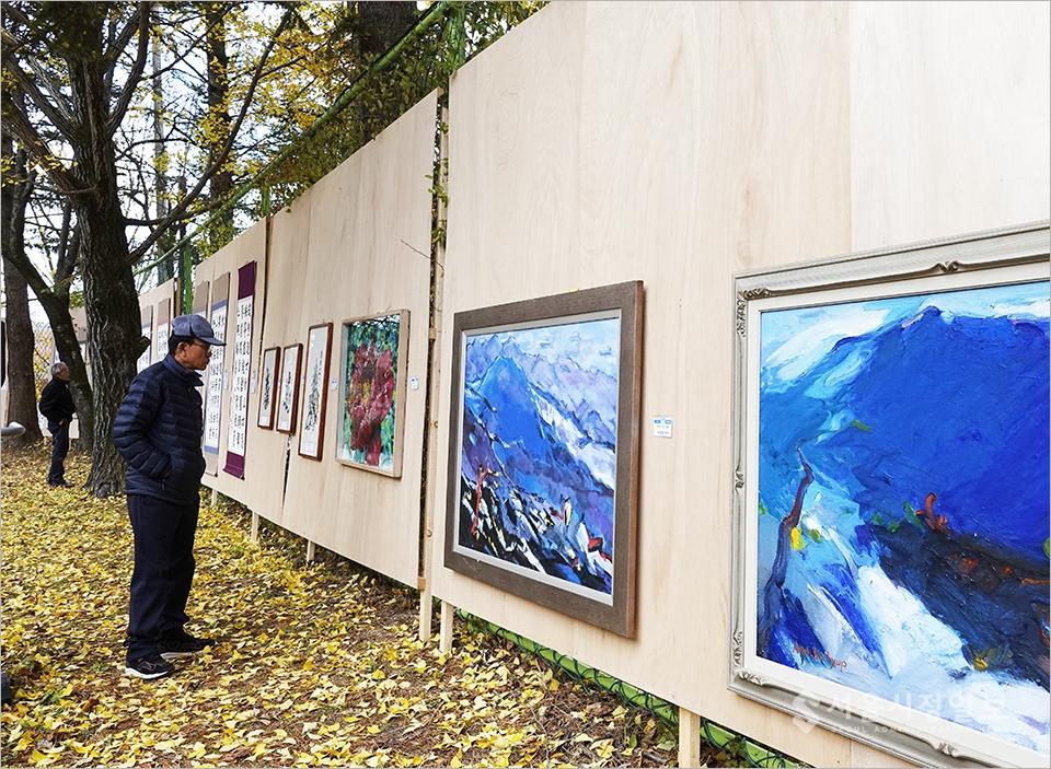 ▲ 미술품을 감상하고 있는 마을주민.
